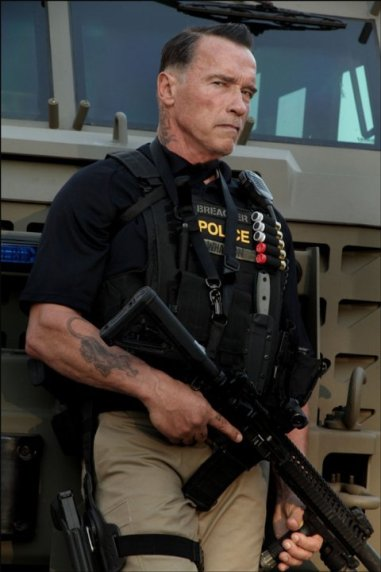 Arnold Schwarzenegger promotional image from Sabotage (2014) he's holding a big gun and looks menacing