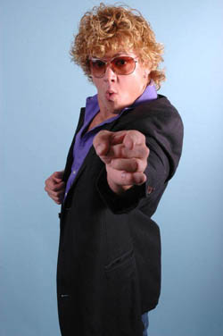 Deceased pro wrestling Larry Sweeney points at the camera wearing a suit and sunglasses