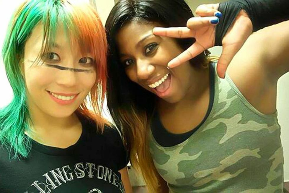 WWE woman wrestlers Asuka and Ember Moon pose together for a selfie, they can be seen from the shoulders up both smiling