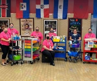 Staff members pose with carts filled with supplies