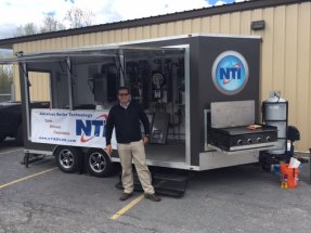 Chris Kelly in front of NTI Trailer