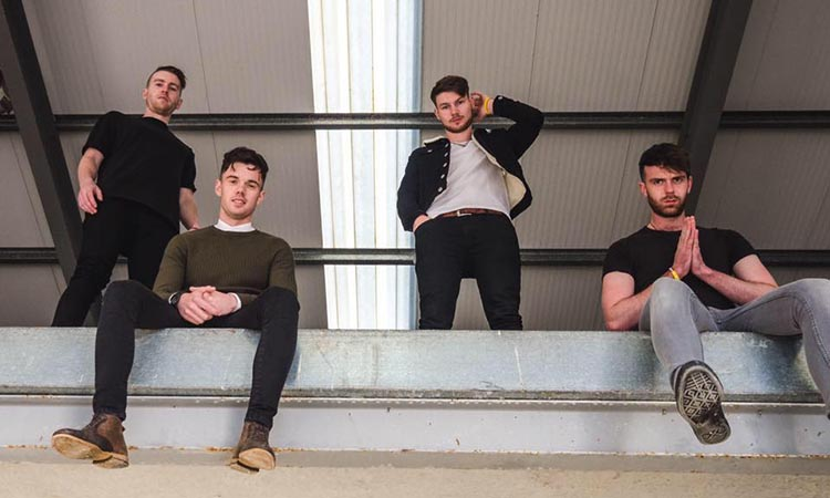 Brave Giant : 4 members of the band pose in an industrial setting, looking down at the camera. Two are sitting, two standing.