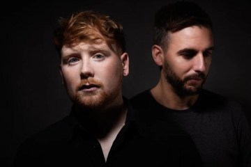 The music duo Exiles pose with a dark moody background for their single Rearview Mirror