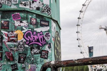 Photo of stickered street furniture with the London Eye in the background