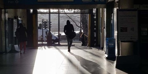 A man walking into the sunlight, casting shadows.
