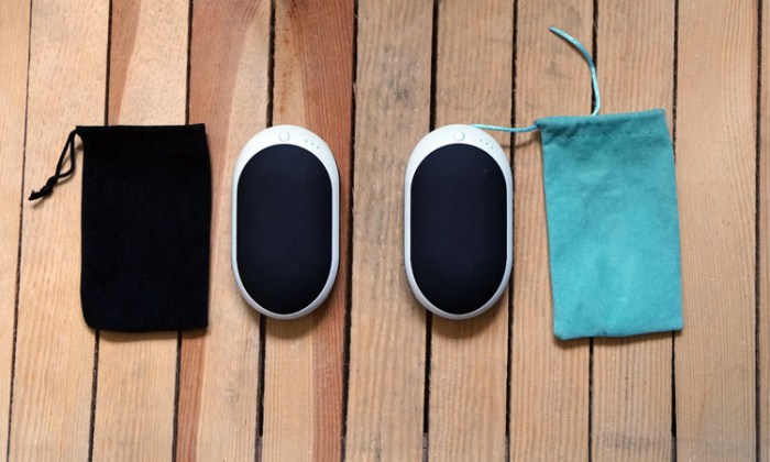 Two Occopa handwarmers with their cloth covers laid out on wood