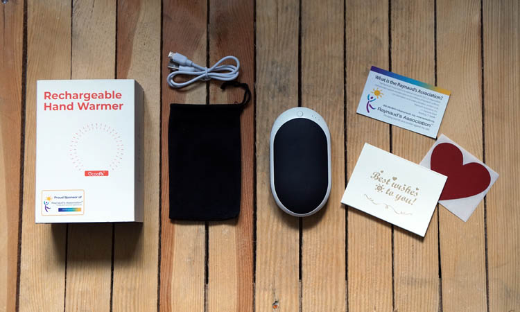 Ocoopa handwarmer laid flat with the presentation box, cloth cover and usb cable with some stickers sent by the company