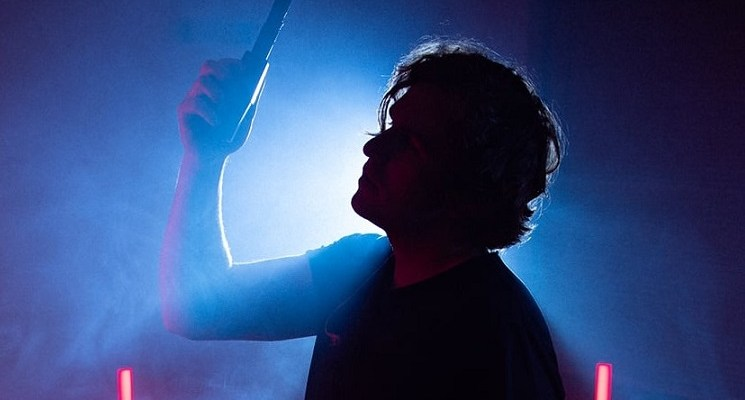 Now Ex in silhouette holding a microphone hanging from above