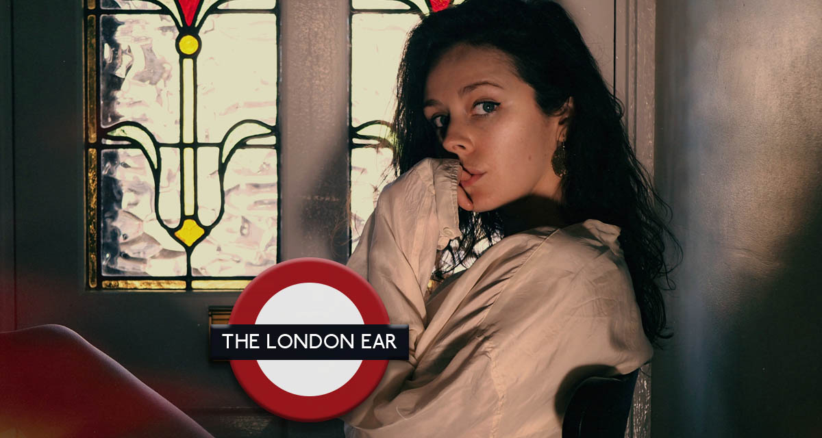 The London Ear - Laura Elizabeth Hughes sitting on a chair in front of a stained