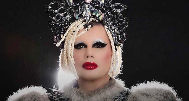 A glamorous Paul Quin, wearing fux fur and a crown sits in front of a black ground