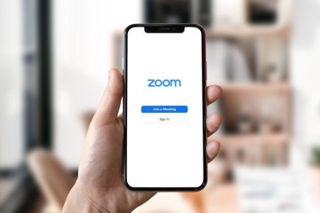 A person holds a phone that displays the Zoom log in page
