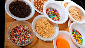 Toppings are ready to add to the chocolate-dipped caramel apples