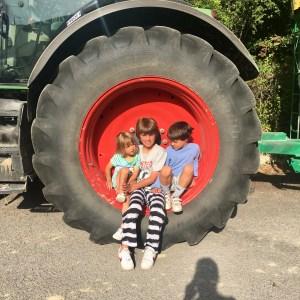 Tres niños sentados en la rueda de un tractor