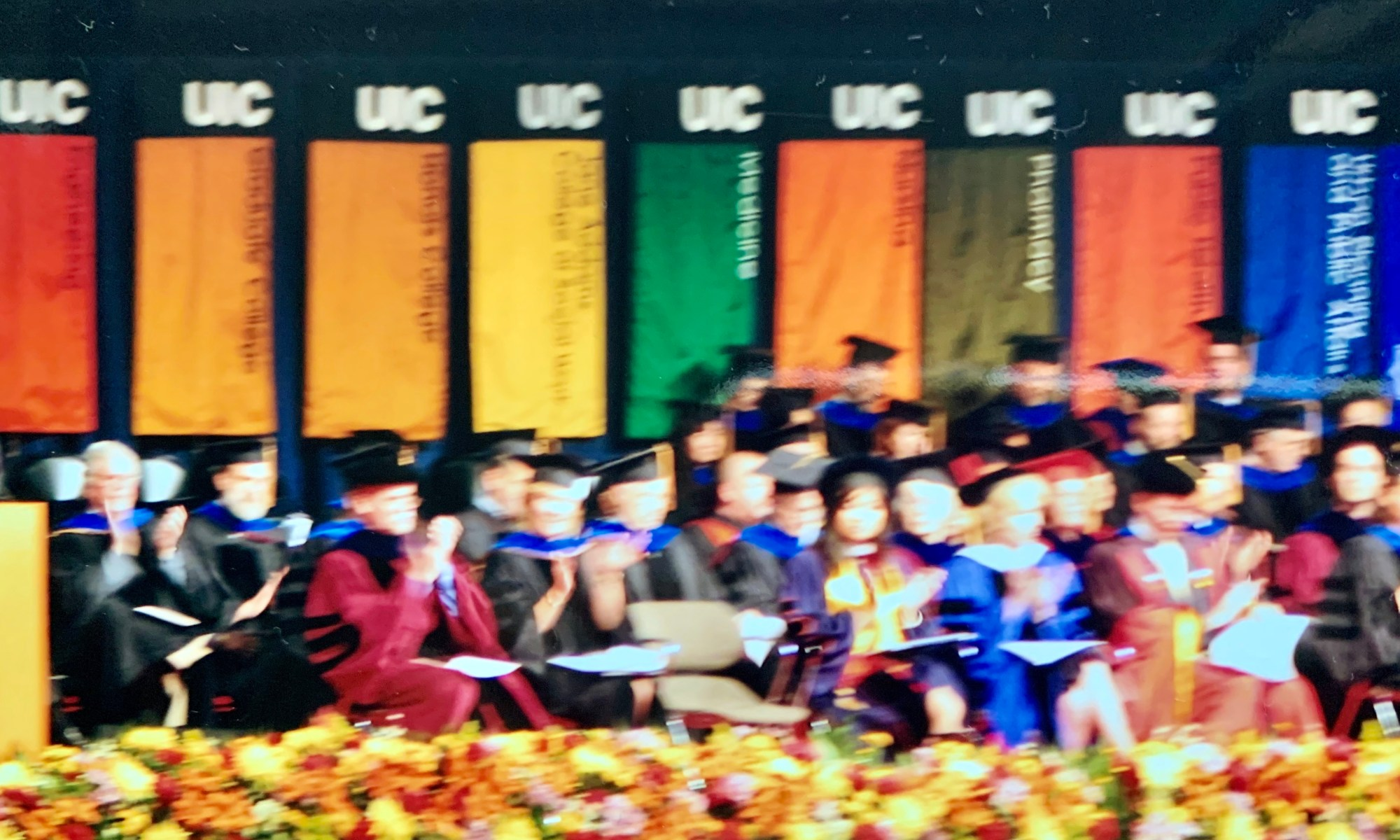 Blurry image of a commencement ceremony, with colorful banners