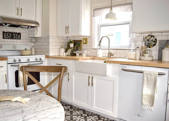 White Kitchen remodel with patterned tile and butcher block counter tops.
