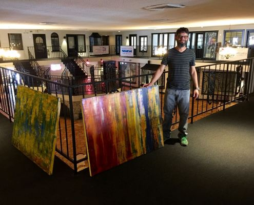 Nestor Toro installing artwork at his solo show in West Hollywood
