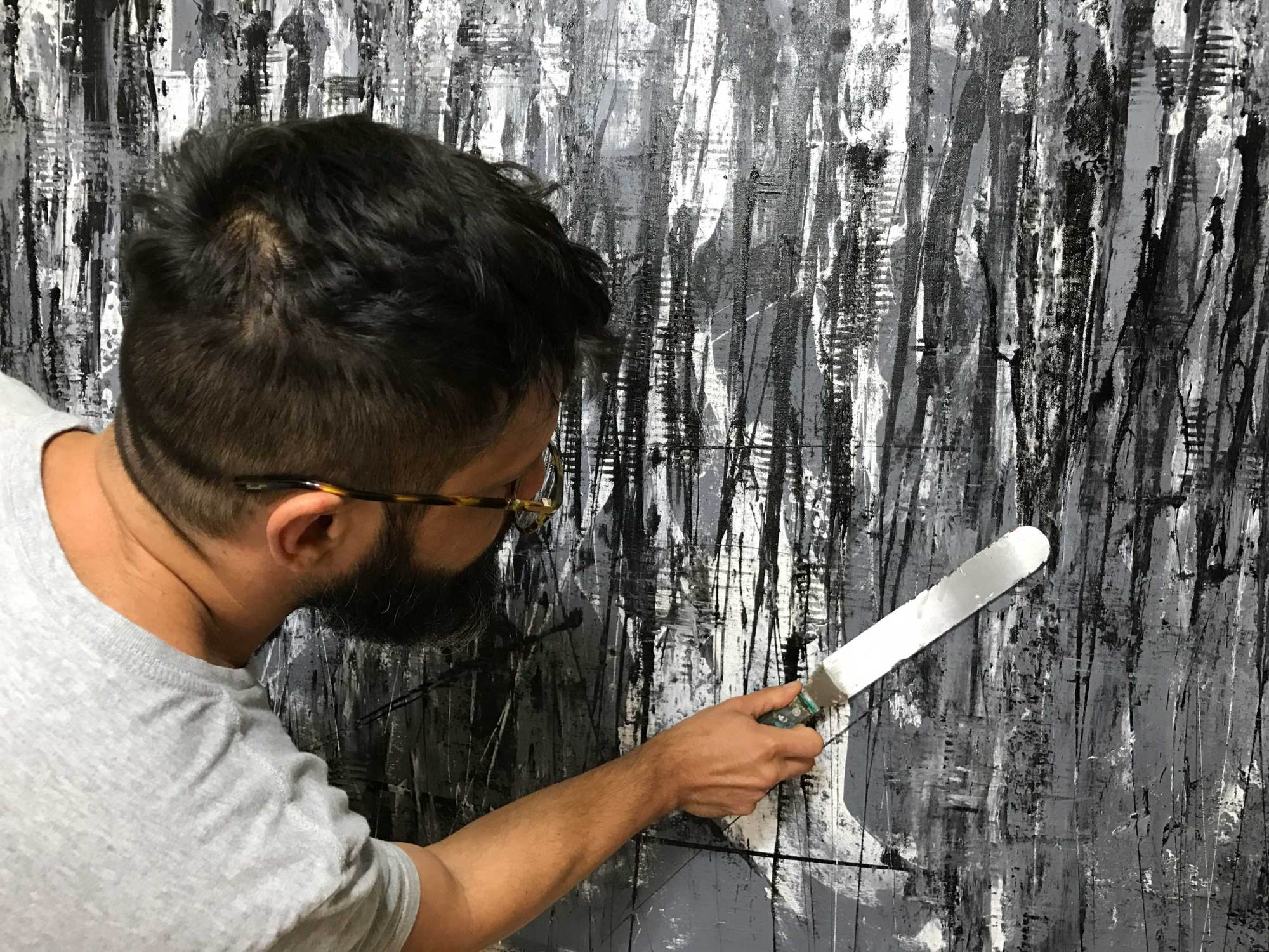 Artist Nestor Toro working on December which is a monochromatic statement work in shades of Grey