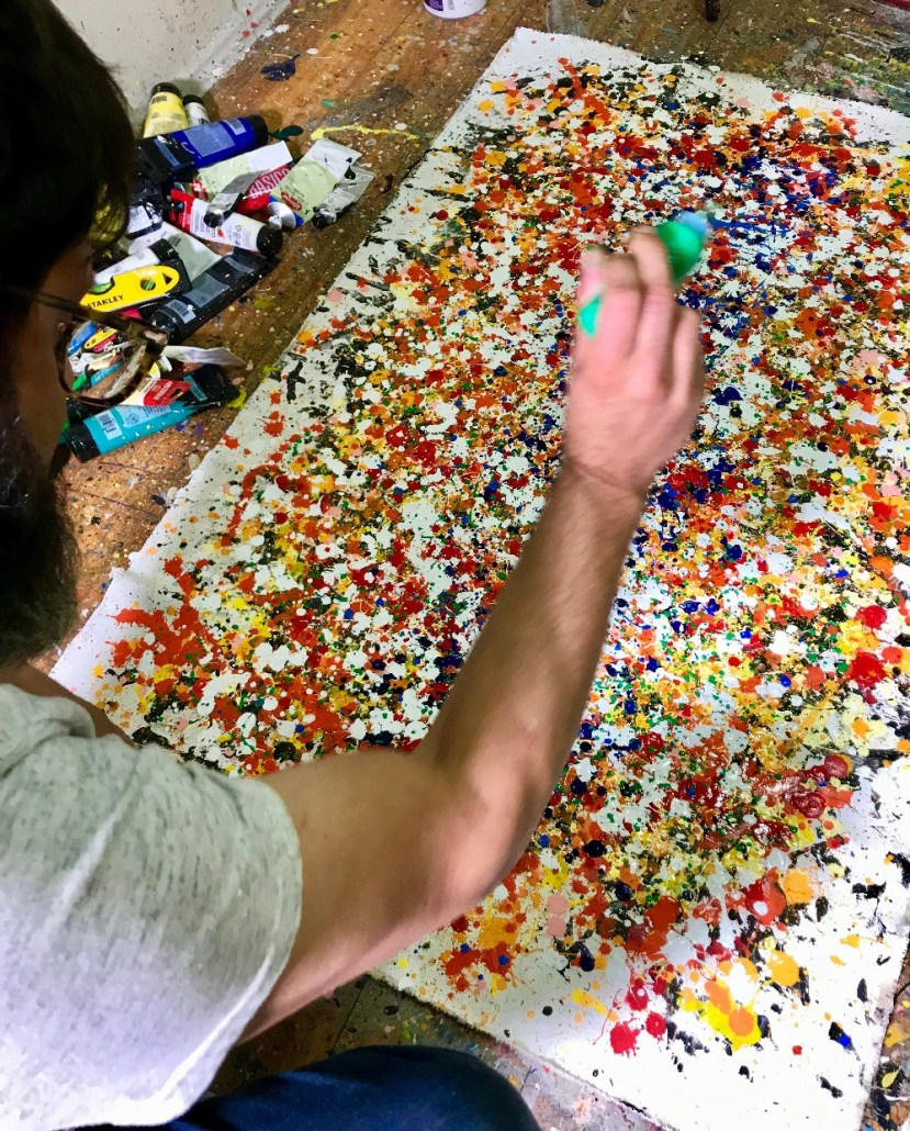 Here is Nestor Toro painting in the studio creating works as he typically does with the canvas on the floor similar to the painting technique of Jackson Pollock.