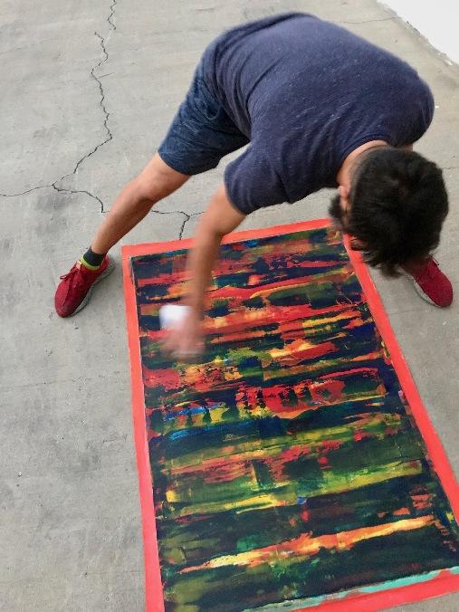 Artist Nestor Toro spraying UV sealer on artwork prior to shipping the artwork to an international collector