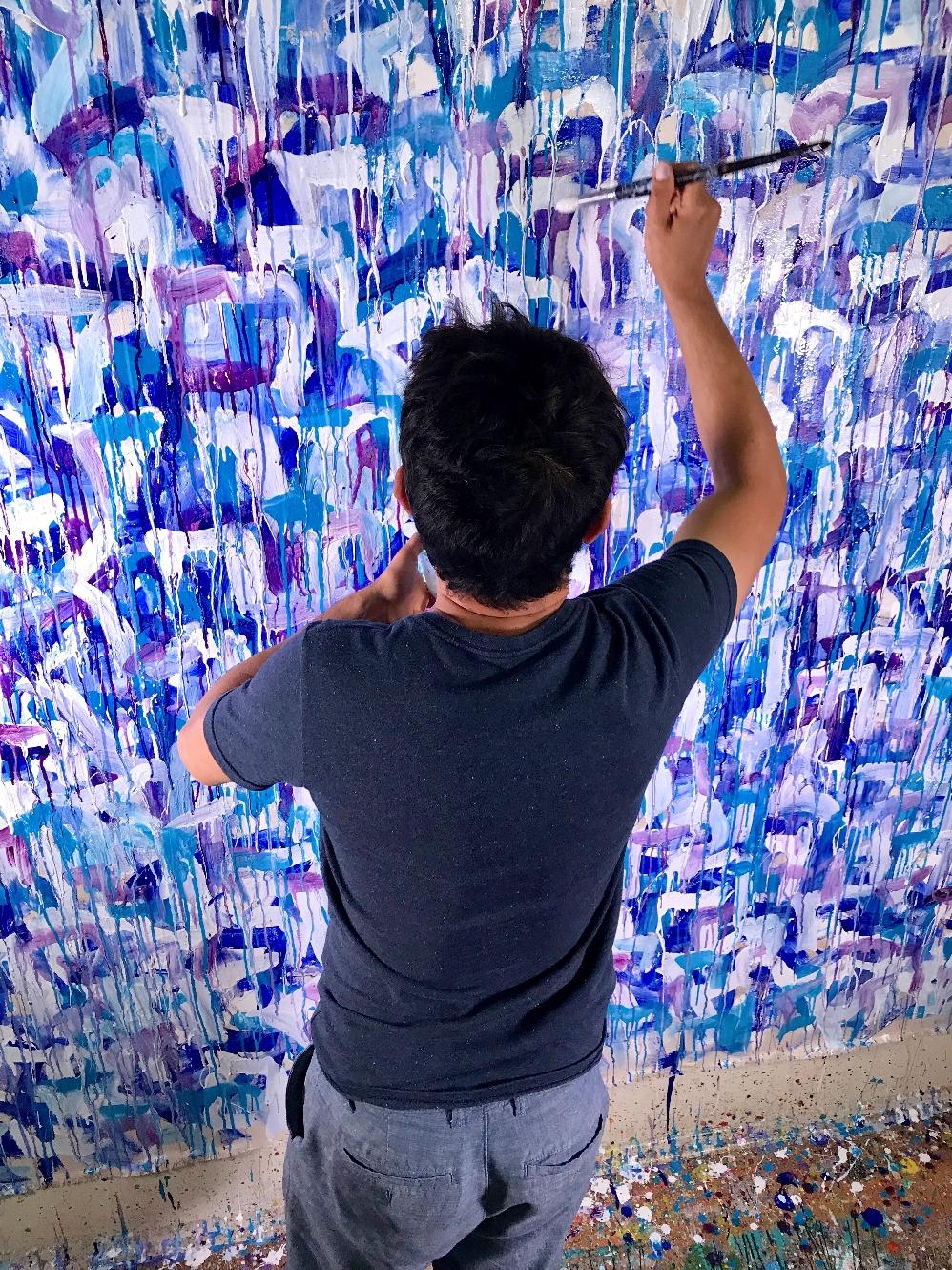 Artist Nestor Toro working on the painting