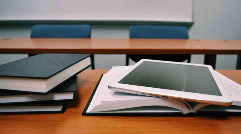 silver ipad on white book page