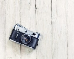 An artistic camera on a white washed background