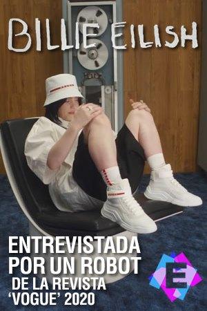Billie Eilish pantalones negro camisa blanca gorra blanca y zapatillas blanca sentada en una silla con un ordenador viejo de fondo.