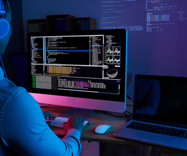 Programmer in headphones checking his code on computer screen