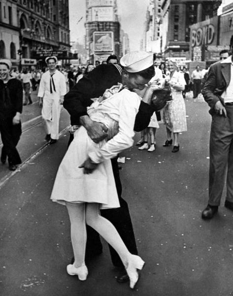 """Caption from the August 27, 1945, issue of LIFE. """"In the middle of New York's Times Square a white-clad girl clutches her purse and skirt as an uninhibited sailor plants his lips squarely on hers."""""""