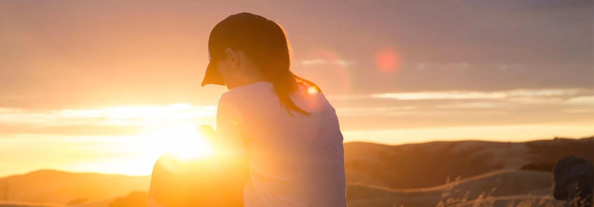 Frau betet im Sonnenuntergang oder Sonnenaufgang