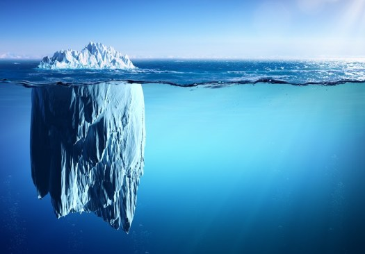 Picture shows an iceberg with a small part above and a great part under the sea level.