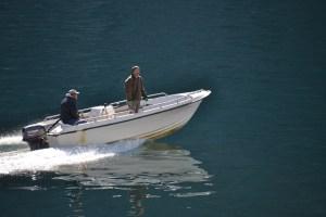 Zwei Männer in einem Kunststoffboot mit Außenborder