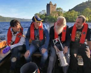 Vier Menschen mit Schwimmwesten im Heck eines Bootes, im Hintergrund Urquhart Castle
