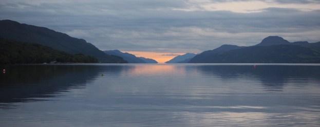 Loch Ness mit Bergketten an beiden Ufern und der Sonne hinter Wolken am gegenüberliegenden Ende
