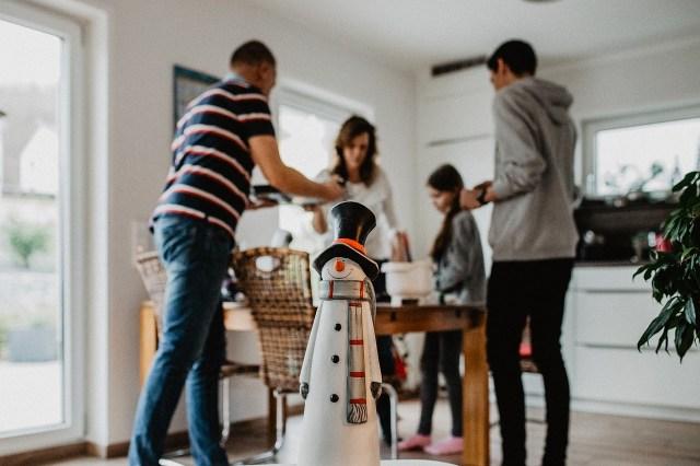 Familie steht um einen Tisch