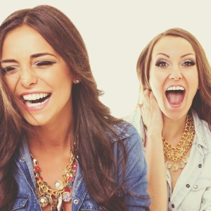 Two happy fashionable young women laughing
