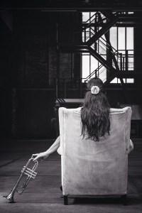 Frau im Sessel mit Trompete. (Foto: Alex, Unsplash.com)