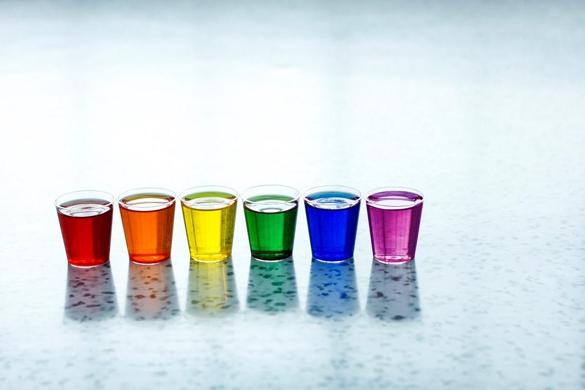 Farbige Flüssigkeiten in kleinen Bechern. (Foto: Andrew Jay, Unsplash.com)
