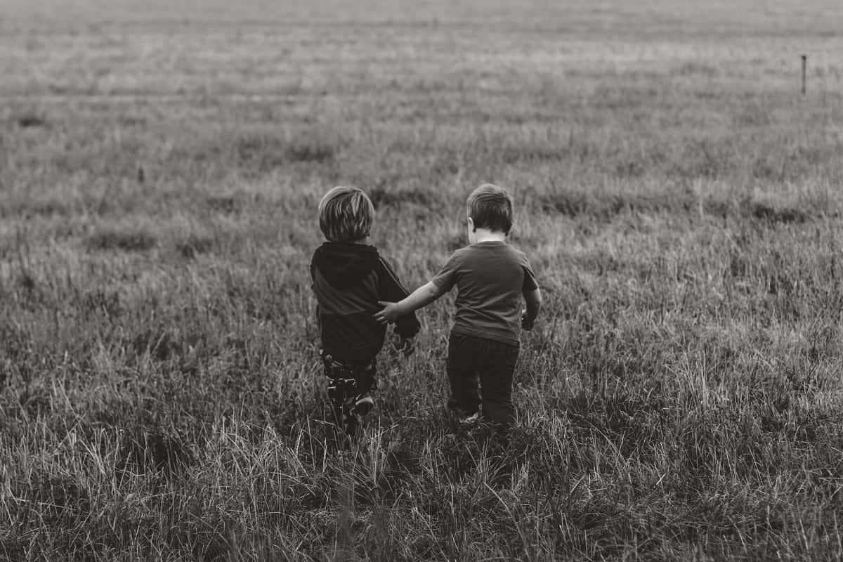 Die Rechte des Kindes kennen keine Grenzen. Zwei Kinder spazieren über eine Wiese. (Foto: Kevin Gent, Unsplash.com)