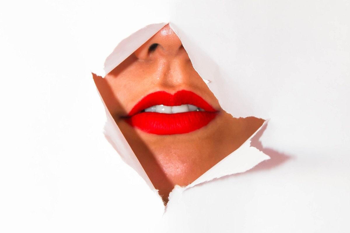 Youtuber bringen sich ins beste Licht. Rote Lippen und gerissenes Papier. (Symbolfoto: Kelsey Curtis, Unsplash.com)