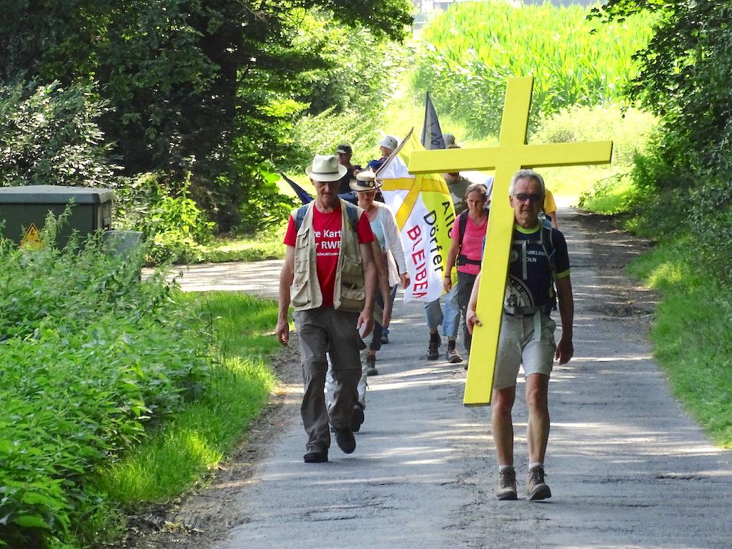 """Keyenberg – Christliche Umweltschützer haben einen 470 Kilometer langen """"Kreuzweg für die Schöpfung"""" von Gorleben bis an den Tagebau Garzweiler beendet. Die Aktivisten kamen am Sonntag an der Kirche in Keyenberg an. Die Ortschaft soll wie bereits andere Dörfer in der Umgebung des Braunkohletagebaus durch den Energiekonzern RWEweichen. """"Ihr habt den weiten Weg gemacht und ihr habt gezeigt, wir sind unterwegs mit unserem Glauben"""", sagte Marie Theres-Jung vom Diözesanrat der Katholiken im Bistum Aachen, an die Pilger gewandt. """"Glaube muss politisch bleiben und wir müssen uns einsetzen für unsere Umwelt und versuchen, das zu retten, was überhaupt noch zu retten ist."""""""