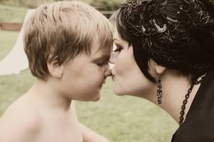 A mother kissing her child's nose.