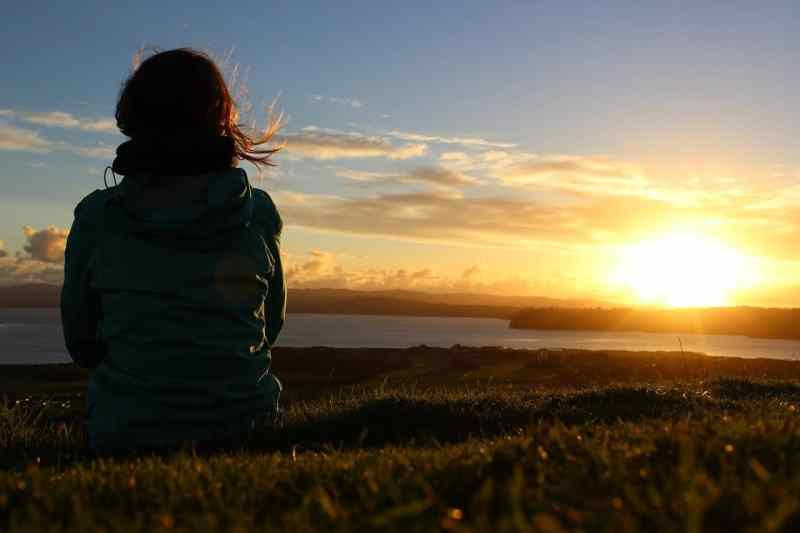 A person sitting in a meadow looking out at the sunset
