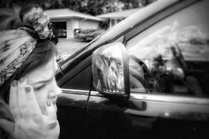 A black and white photo of a woman looking at her reflection on the back of car's side-mirror.