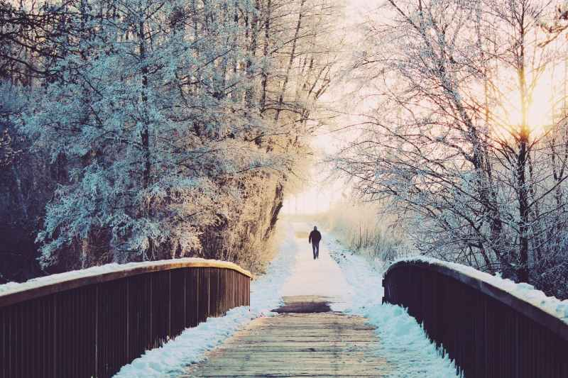 Man walking away from a bridge and down a path surrounded by snow laden trees