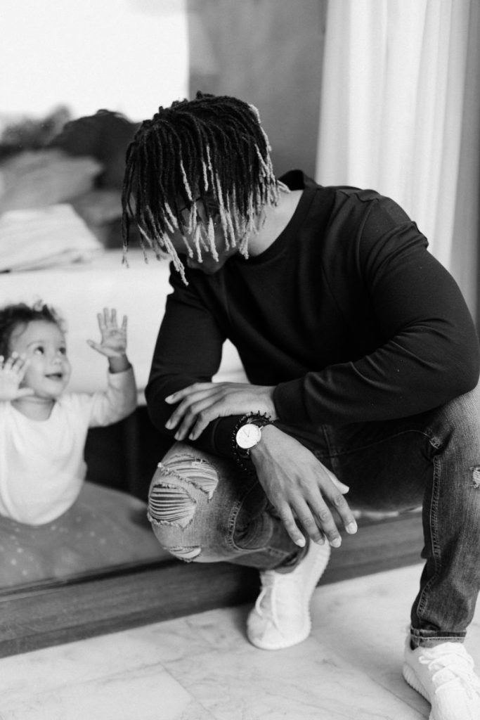 Black and white picture of black father playfully looking at his toddler through a glass door while crouching.