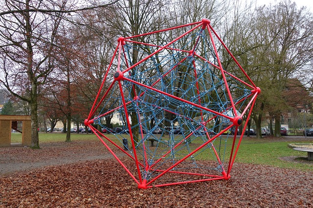 Picture of playground equipment, a hollow dodecahedron made of metal bars.