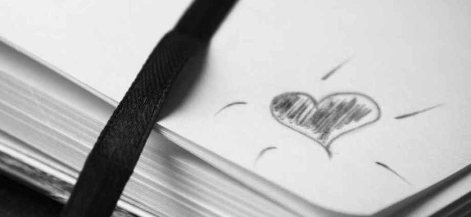 Printer paper with heart drawn on it in black ink, filled in.