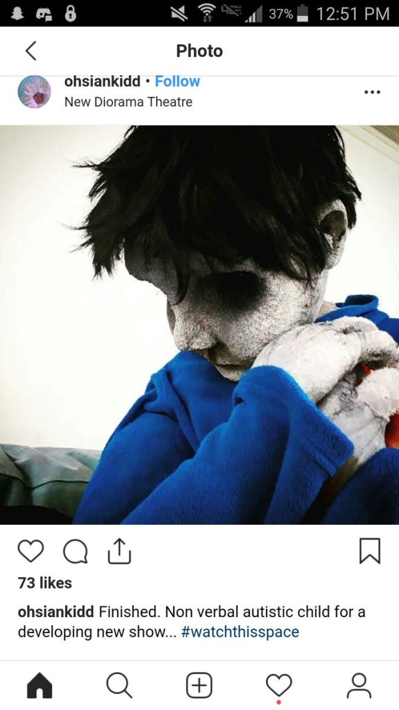 Puppet has grey skin, black pits for eyes, and black hair. It looks like a zombie.