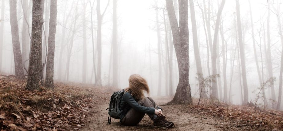 Person with hair covering their face, moving their head sitting on the ground in the woods.